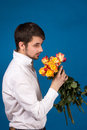 Man with bouquet of red roses on blue background Stock Images