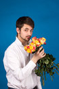 Man with bouquet of red roses on blue background Royalty Free Stock Photo