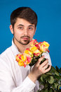 Man with bouquet of red roses on blue background Royalty Free Stock Photos