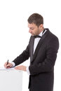 Man in a bow tie completing a form stylish middle aged and suit standing at pedestal pausing to read the document with pen Royalty Free Stock Images