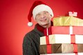 Man with boxes portrait of happy in santa cap stack of giftboxes looking at camera Royalty Free Stock Photo