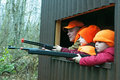 Man and boys looking out of deer stand with guns dad sons pointing their rifles a during a practice hunt Stock Image
