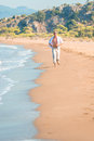 Man in bright clothing runs along the beach line Royalty Free Stock Image
