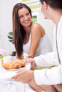 Man bringing breakfast in bed surprising a women with Stock Photography
