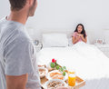 Man bringing breakfast to his impressed wife in bed Royalty Free Stock Photos