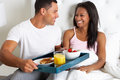 Man bringing woman breakfast in bed on tray smiling to each other Stock Photography