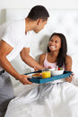 Man bringing woman breakfast in bed on tray smiling to each other Stock Image