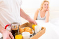 Man bringing young attractive woman breakfast in bed view of a women Stock Image