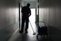 Man with broom cleaning office corridor