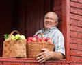 Man brought apples happy elderly with baskets full of Royalty Free Stock Photography