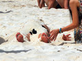 Man buried in sand on the beach by young woman Stock Photos