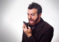 Man in business suit shouting into his mobile phone concept Stock Images