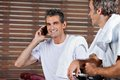 Man on call while friend looking at him in health portrait of happy mature men club Royalty Free Stock Photos