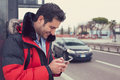 Man calling a taxi with a smartphone app standing along the road Royalty Free Stock Photo