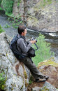image photo : Man with camera on the rock over mountain river.