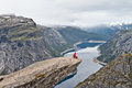 Man with camera sitting on Trolltunga rock Troll`s Tongue rock Royalty Free Stock Photo