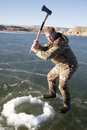 Man in camo chopping hole in ice with axe swing Stock Photo