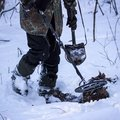 stock image of  Man with a metal detector and a sapper shovel is looking for something in the winter forest