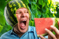Man in a cap from a watermelon bizarre eating outdoors Royalty Free Stock Photo