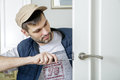 Man carpenter fixing lock in door with screwdriver at home white close up Stock Photo