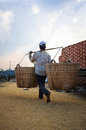 Man carrying a basket of rice husk brick kiln factory cloud sky with rays mekong delta vietnam Stock Photo