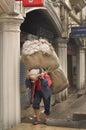 Man carrying big sack on street, morning view of Darjeeling, India as of April 12, 2012