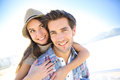 Man carrying girlfriend on his back giving piggyback ride to at the beach Stock Photos