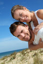 Man carrying his girlfriend on back on the beach giving piggyback ride to a sand dune Stock Photography