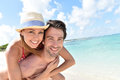 Man carrying his girlfriend on the back by the seaside giving piggyback ride to caribbean beach Stock Photography