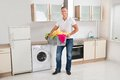 Man carrying laundry basket in kitchen room young happy multi colored clothes Royalty Free Stock Photo