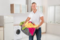 Man carrying laundry basket in kitchen room young happy multi colored clothes Royalty Free Stock Image