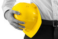 Man carrying a yellow hard hat close up of the hand of professional against his hip with selective color conceptual of an Royalty Free Stock Images