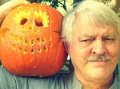 Man with carved halloween pumpkin senior poses proudly his finished Royalty Free Stock Photo