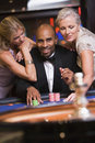 Man in casino with glamorous women Royalty Free Stock Photography