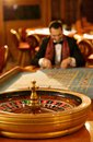 Man in casino interior suit and scarf playing roulette a Royalty Free Stock Images