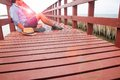 A man in casual clothing sitting alone on wooden bridge Royalty Free Stock Photo