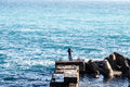 Man catches fish in the sea stands on concrete blocks Royalty Free Stock Photo