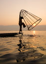 A man catching fish at sunrise on the lake in Inlay, Myanmar Royalty Free Stock Photo
