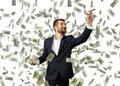 Man cathing dollar s smiley young businessman standing under money rain and Royalty Free Stock Photography