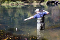 Man caught on bait rainbow trout and stretches to get it out of the water Stock Photos