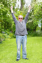 Man celebrating retirement senior with hands in the air his on his green grass garden lawn Royalty Free Stock Images