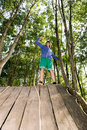 Man celebrating success after climbing wooden slope low angle view of young in forest Royalty Free Stock Images