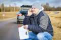 Man with cell phone and empty can waiting for help near car Royalty Free Stock Photo