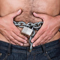 Man with a chain and padlock around his stomach symbolizing dieting or fasting Stock Images