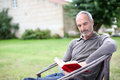 Man in chair reading book outdoor senior novel country home garden Stock Images