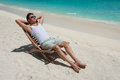 Man in chair sunbathing on the beach near the sea Royalty Free Stock Photo