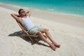 Man in chair sunbathing on the beach near the sea Royalty Free Stock Photo