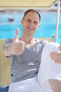 Man in a chaise lounge resting against swimming pool and giving thumbs up sign Stock Photography