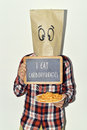 Man with chalkboard with text i eat carbohydrates a young caucasian a paper bag in his head a funny face shows a the and a Royalty Free Stock Photo
