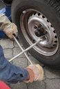 Man changing a car tyre unscrew screw nut Royalty Free Stock Photos